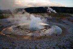 Losbarstende geiser: de wolken dachten in een vijver van hete die de lentereproductie door witte hydrothermale korst wordt omring Stock Afbeeldingen