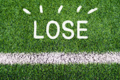 LOSE hand writing text on soccer field grass Stock Photos