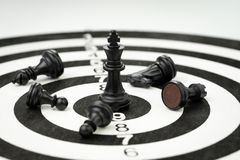 Lose some to win some metaphor in business success strategy or l. Eadership concept, black winner chess king at the center of dartboard surrounded by injure or Royalty Free Stock Image