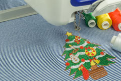 Lose up embroidery machines workspace and Christmas tree. Background of close up embroidery machines workspace and Christmas tree cartoon style on blue fabric Stock Photos