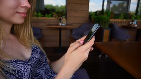 Lose up hands typing message by smartphone at cafe. Close up hands typing message with smartphone at cafe. Gladden woman smiling, chatting and waiting for food stock video footage