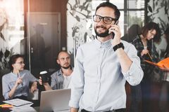 Сlose up photo of smiling bearded businessman wearing glasses w. Hile talking on smartphone with customer. Discussion of project by phone in the teem coworking Royalty Free Stock Photo