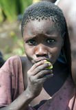 Сlose-up portrait cute african girl of the hadza tribe. AFRICA, TANZANIA, MAY, 10, 2016 - Сlose-up portrait  cute african girl of the hadza tribe, that eats Stock Image
