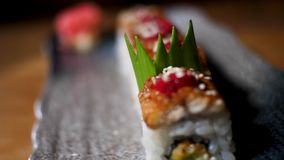 Lose up for sushi rolls on black tray standing on the table, Japanese traditional food. Frame. Delicious decorated stock images