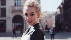 Сlose up view of a young woman in elegant wear and red lips walking in the city-center, then turning to camera and stock footage