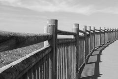 Lose up on wooden fence on the walkway on atlantic coast in black and white, saint jean de luz, basque country, france. View on wooden fence on the walkway on stock photography