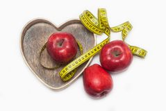 Lose Weigh. Close Up of Measuring Yellow Tape Ties Around Red Apples in Wooden Heart shape box. Isolated on white background. hori Royalty Free Stock Images