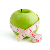 Lose weight. Green apple wrapped dressmaker meter isolated on a white background Stock Photos