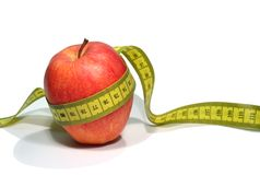 Lose weight. An apple with a measuring tape stock photography