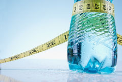 Lose weight. Bottle of water wrapped with tape measure Stock Images