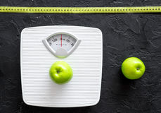 Lose weight concept. Bathroom scale, measuring tape, apples on black background top view Royalty Free Stock Photography