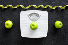Lose weight concept. Bathroom scale, measuring tape, apples on black background top view.  stock images