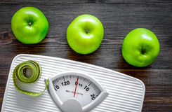 Lose weight concept. Bathroom scale, measuring tape, apples on wooden background top view Royalty Free Stock Images