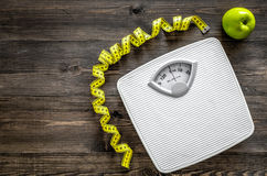 Lose weight concept. Bathroom scale, measuring tape, apples on wooden background top view copyspace Royalty Free Stock Photo