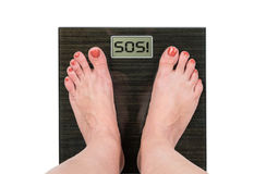 Lose weight concept. Female measuring weight with scale, sos sign on display Royalty Free Stock Photography