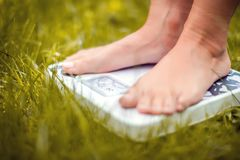 Lose weight concept. A person on a scale on a grass measuring kilograms. Outdoor stock image