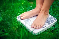 Lose weight concept. A person on a scale on a grass measuring kilograms. Outdoor royalty free stock photo