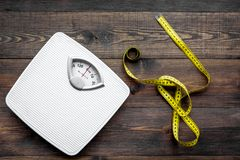 Lose weight concept. Scale and measuring tape on dark wooden background top view.  royalty free stock photo
