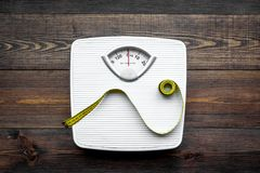 Lose weight concept. Scale and measuring tape on dark wooden background top view.  royalty free stock photography