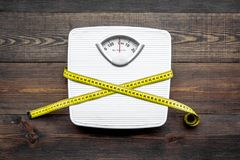 Lose weight concept. Scale and measuring tape on dark wooden background top view.  royalty free stock photos