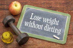 Lose weight without diet. Motivational words on a slate blackboard against weathered red painted barn wood with a dumbbell, apple and tape measure Stock Image