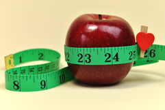 Lose Weight New Year Resolution Goal Closeup. New Year Resolution Goal Lose Weight Weightloss Diet Concept. Bright red apple with green measuring tape against a Royalty Free Stock Photos