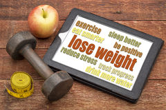 Lose weight - tips on a tablet. Lose weight - tips on a digital tablet with a dumbbell, apple and tape measure Stock Photo