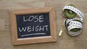 Lose weight. Written on a chalkboard next to a kiwi an inches Royalty Free Stock Photo