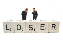 Loser. Two businessmen standing behind the word loser stock image