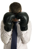 Loser businessman covers his face boxing gloves. Loser businessman covers his face with boxing gloves, isolated on white Royalty Free Stock Images