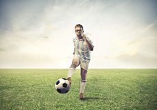 Loser Football Player. A loser football player is kicking a football ball Royalty Free Stock Photos