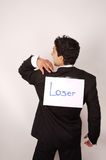 Loser - Removing the sign. Young male Removing a 'Loser'  sign posted on his back Stock Photography