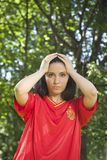 Loser spanish football supporter. Young woman with red spanish football team shirt unhappy Royalty Free Stock Photo