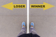 Loser vs Winner text arrows on asphalt ground, feet and shoes on Stock Image