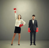 Loser and winner. Businessman loser and winner businesswoman in red boxing gloves over dark grey background Stock Photos