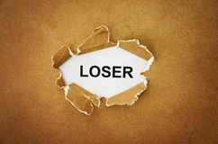 Loser. The word loser in the hole of brown paper Stock Image
