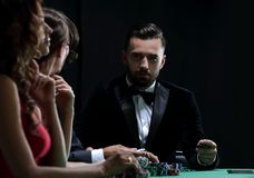 Upper class friends gambling in a casino. Losers and winners. Group of rich people is playing poker in the casino stock photography