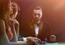 Upper class friends gambling in a casino. Losers and winners. Group of rich people is playing poker in the casino royalty free stock image