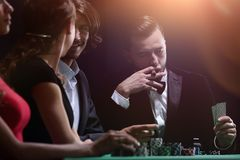 Upper class friends gambling in a casino. Losers and winners. Group of rich people is playing poker in the casino stock images