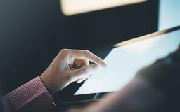 Loseup ¡ Ð человека указывая к монитору компьютера с синью пустого экрана против предпосылки света bokeh в офисе стоковое изображение rf