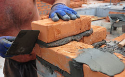 Сloseup of a bricklayer worker installing red bloks and caulking brick masonry joints exterior wall with trowel putty knife. A closeup of a bricklayer worker Royalty Free Stock Image