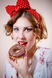 Сloseup portrait of beautiful blond young woman with excellent dental care teeth having fun eating donut and happy smiling. Picture of pinup girl with excellent Stock Image