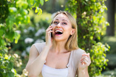 сloseup of positive young woman talking on mobile phone outdoor Stock Photography