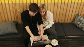 Losgemaakt paar die laptop computer in koffiewinkel met behulp van stock video