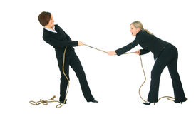 Losing Competition. Two businesswomen struggle pulling rope with each another, one is winning and the other is losing. concept for competition stock photo