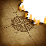 Losing Direction. And bad business planning and strategy with a compass rose navigation symbol on an old grunge parchment texture burning in flames as confused Royalty Free Stock Photo
