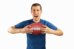 Losing football player. Cropped portrait of a young american football player shouting passionately while holding the match ball isolated on white background Stock Photography