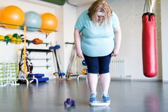 Losing Kilos in Gym. Full length portrait of big overweight woman standing on scales after fitness training, copy space stock photos