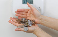 Losing money due to heating home cost. Close up of female hands spilling money due to heating costs. Financial loss of money concept Stock Photos