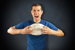 Losing soccer player. Portrait of loser angry and aggressive player football holding a soccer football over a  black blackboard background with copy space for Stock Photography